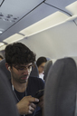 Young man in a plane with cell phone and earbuds - KKAF01775