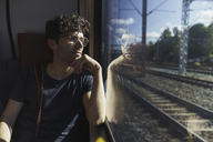 Man traveling by train looking out of window - KKAF01778
