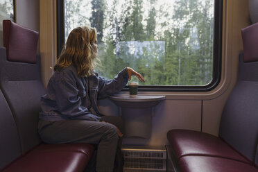 Woman traveling by train looking out of window - KKAF01784