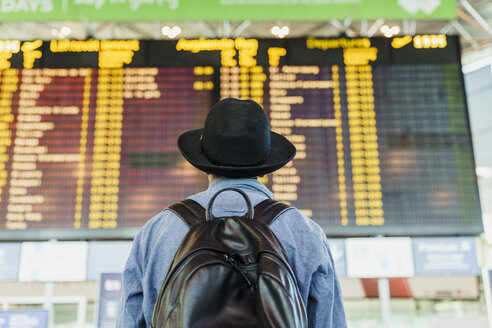 Young man with hat and backpack looking at arrival departure board at the airport - KKAF01790