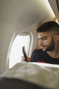 Young man in a plane with cell phone - KKAF01796