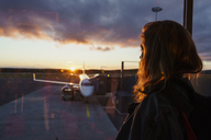 Young woman looking through window on plane at the airport at sunset - KKAF01802