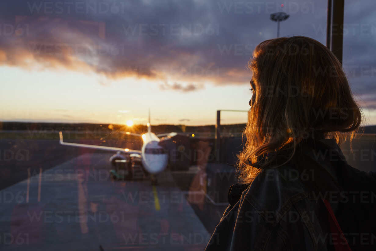 Young woman looking through window on plane at the airport at sunset - KKAF01802 - Kike Arnaiz/Westend61