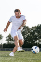 Young man kicking soccer ball - STSF01740