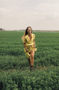 Young woman walking in a green field - ACPF00343