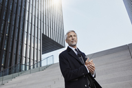 Portrait of mature businessman standing on stairs outdoors - RORF01470