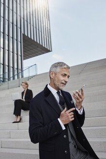 Portrait of businessman talking on the phone while business woman working on laptop in the background - RORF01473