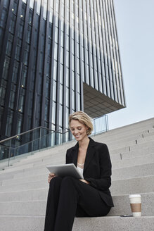 Blond businesswoman with coffee to go sitting on stairs in front of modern office building using tablet - RORF01479