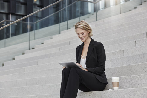 Blond businesswoman with coffee to goe sitting on stairs using tablet - RORF01482