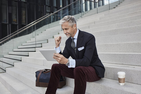 Fashionable businessman with travelling bag nd coffee to go sitting on stairs using tablet - RORF01497