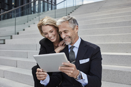 Portrait of two laughing businesspeople sitting together on stairs looking at tablet - RORF01500