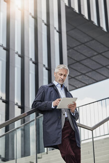 Portrait of mature businessman standing on stairs in front of modern office building using tablet - RORF01506