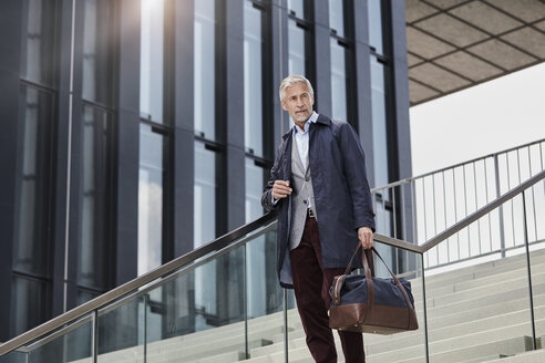 Portrait of mature businessman with traveling bag standing on stairs outdoors - RORF01509