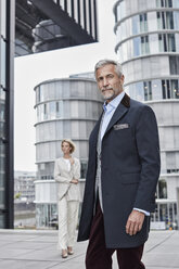 Germany, Duesseldorf, portrait of fashionable mature businessman in front of modern business building - RORF01530