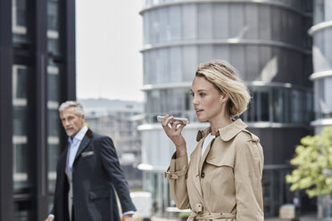 Germany, Duesseldorf, portrait of  blond businesswoman wearing beige trenchcoat talking on mobile phone - RORF01536