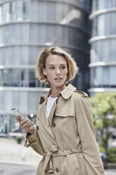 Germany, Duesseldorf, portrait of  blond young businesswoman with smartphone wearing beige trenchcoat - RORF01539