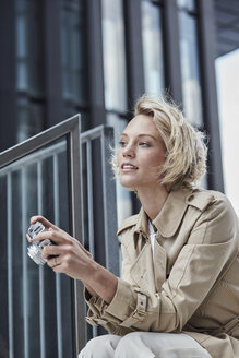 Portrait of young blond woman with digital camera sitting on stairs - RORF01548