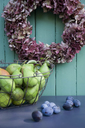 Wreath with hortensias, pears in wire basekt and plums on wood - GISF00385