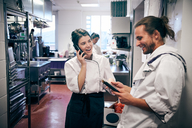 Male and female chefs using cordless phone and digital tablet in kitchen - MASF08654