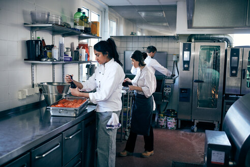 Female chef seasoning tomatoes while standing at kitchen counter - MASF08663