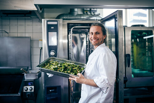 Portrait of confident chef with broccoli in baking sheet at commercial kitchen - MASF08666