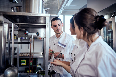 Male chef taking notes while looking at colleagues cooking in commercial kitchen - MASF08672