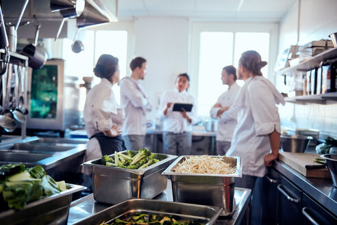 Vegetables in containers with chef team discussing in background at kitchen - MASF08675
