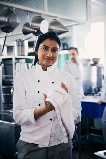 Portrait of confident female chef wiping her hands with napkin in kitchen - MASF08684