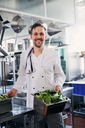 Portrait of smiling male chef holding containers of vegetables in kitchen - MASF08690