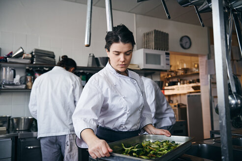 Mid adult female chef holding baking sheet with broccoli at commercial kitchen - MASF08696