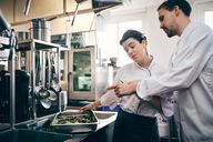 Male and female chefs reading order ticket while preparing food in commercial kitchen - MASF08699