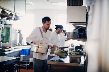 Young male chef carrying containers of food in commercial kitchen - MASF08702