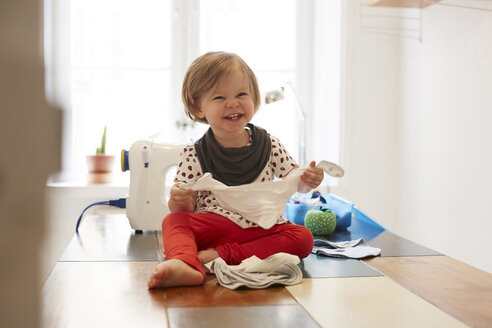 Cheerful girl wearing scarf while sitting on table against sewing machine at home - MASF08720