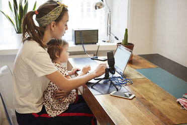 Podcaster sitting with daughter while marketing through laptop at home - MASF08732