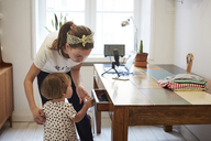 Podcaster looking at daughter opening drawer while standing by table - MASF08735