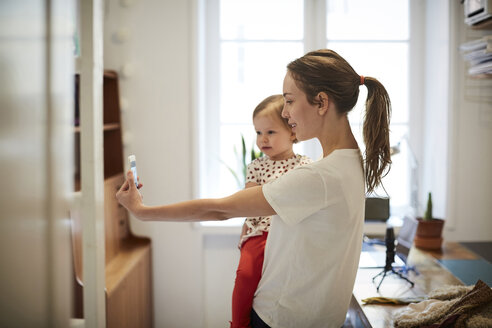 Female influencer taking selfie with daughter through smart phone at home - MASF08738