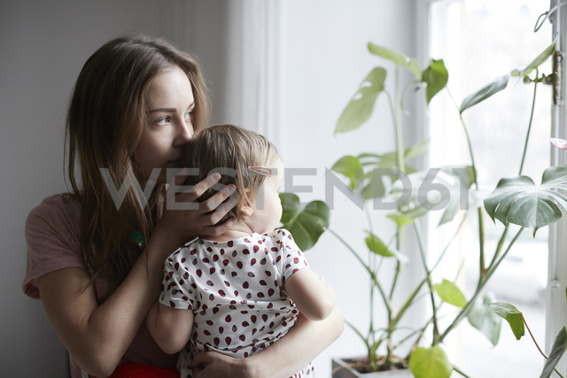 Mother kissing daughter while looking through window at home - MASF08741 - Maskot ./Westend61