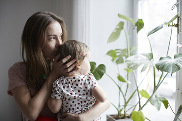 Mother kissing daughter while looking through window at home - MASF08741