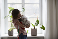Side view of fashion designer embracing daughter while standing at home - MASF08744