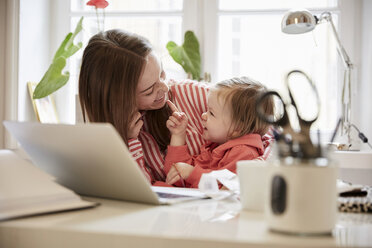 Smiling woman talking to daughter while working on laptop at home - MASF08762