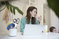 Blogger with laptop drinking water while looking at daughter - MASF08771