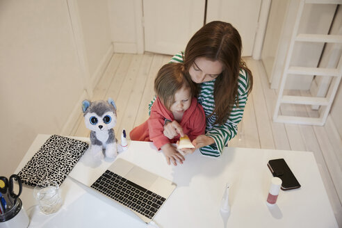 High angle view of blogger holding beauty product while sitting with daughter at table - MASF08774