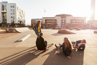 Girl standing while talking to teenage friends sitting at skateboard park during sunny day - MASF08813
