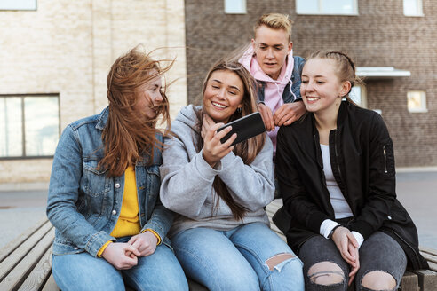 Smiling teenage girl taking selfie with friends through mobile phone against building - MASF08825