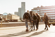 Rear view of friends with bicycle and skateboard on pedestrian zone in city against sky - MASF08831