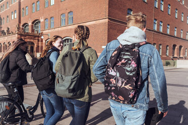 Rear view of teenage friends walking together on footpath in city - MASF08837