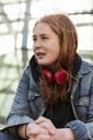 Teenage girl in denim jacket with red headphones looking away - MASF08840