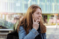 Smiling teenage girl talking on mobile phone while looking away in city - MASF08855