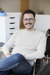 Portrait of smiling businessman sitting on chair at office - MASF08876