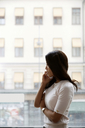 Side view of businesswoman talking on mobile phone while standing by window at office - MASF08879